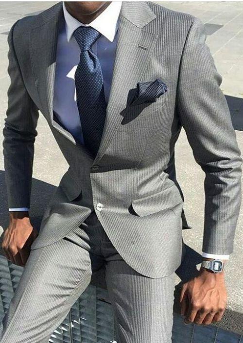 Grå kostym för män med blå skjorta och matchande blå slips.  #affär.
