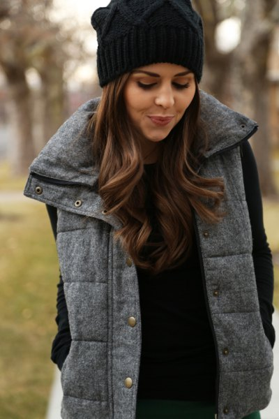 svart stickad mössa med en grå quiltad lång väst och stickad tröja