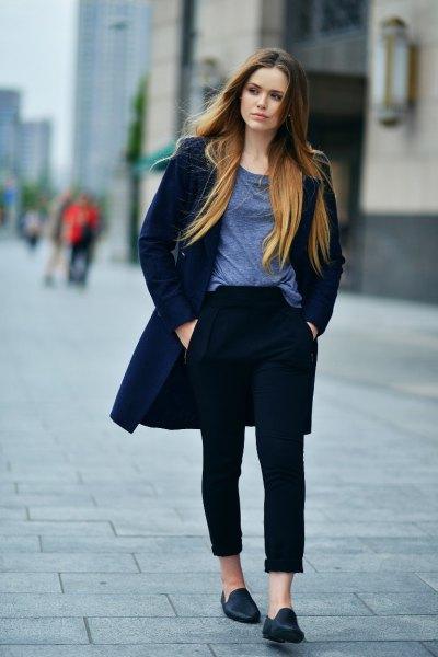 Mörkblå långfodrad ulljacka med svarta jeans med muddar och tofflor av öre mocka