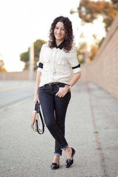 vit skjorta med knappar, svart krage och smala jeans med mörka manschetter