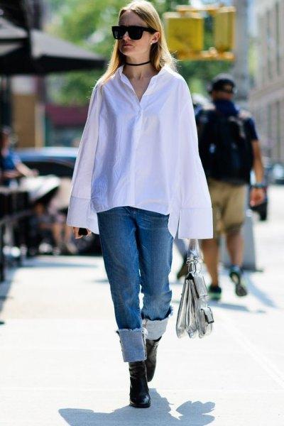 vit bred långärmad skjorta med knappar och blå jeans med raka ben och ärmslut
