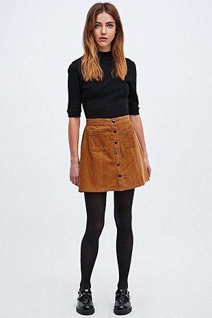 svart mock-neck tröja med halva ärmar och brun corduroy mini kjol med knappfäste