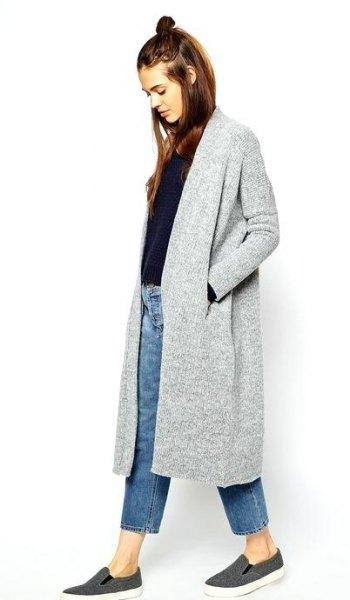 grå lång kofta med svart tröja och blå ankeljeans