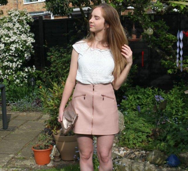Virkad spets med vita kepsärmar och rosa minikjol i läder med dragkedja framtill