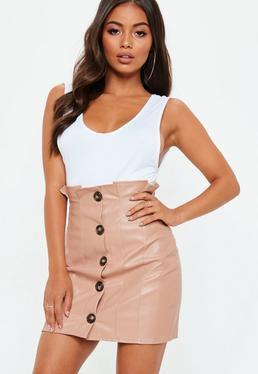 vit linne med scoop-halsringning och rosa minikjol med hög midja och knappknäppning