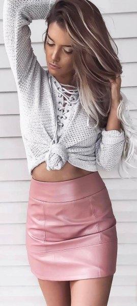 Ljusgrå stickad tröja med en rosa figurkramande minikjol i läder