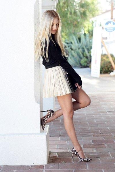 svart stickad tröja med stand-up krage och vit veckad kjol