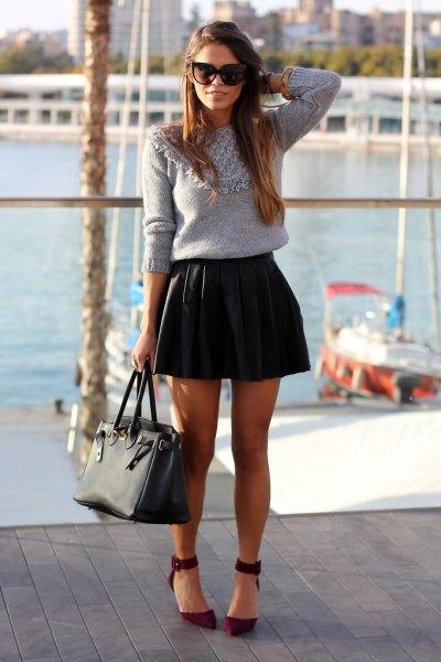 grå stickad tröja med svart läderplisserad kjol i läder