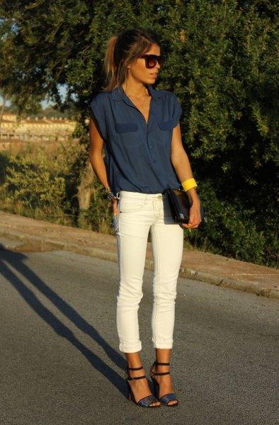 Mörkblå ärmlös blus med vita jeans med muddar