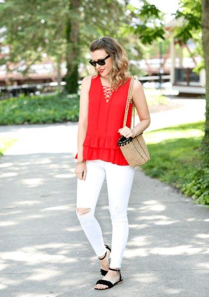 Röd ärmlös blus med V-ringning och vit riven front med vita jeans
