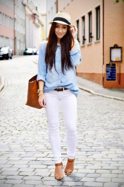 ljusblå chambray-skjorta med vita skinny jeans och en stråhatt
