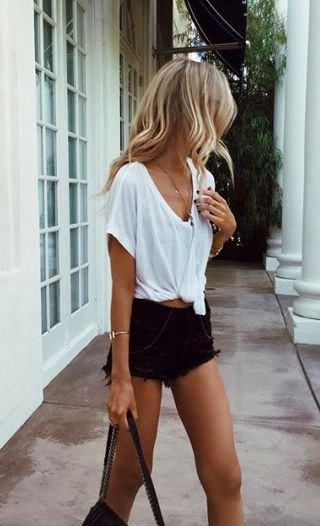 vit knuten V-ringad t-shirt och rippade svarta jeansshorts