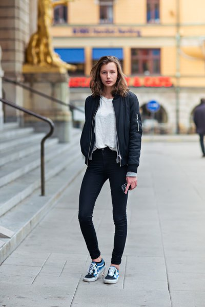 svart bomberjacka med mörka skinny jeans och mörkblå skor
