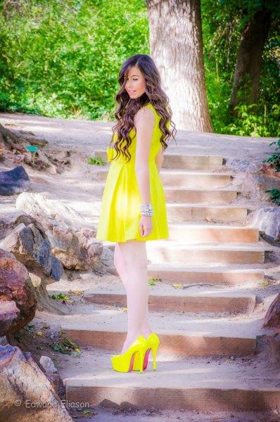 gul ärmlös utsvängd miniklänning med matchande höga klackar