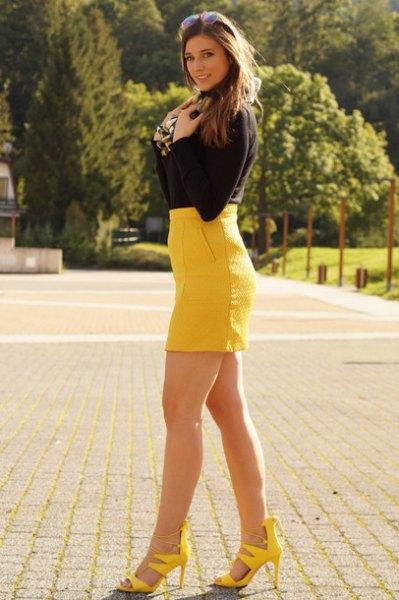 svart tröja med en gul, hög midja, figurkramande minikjol och matchande klackar