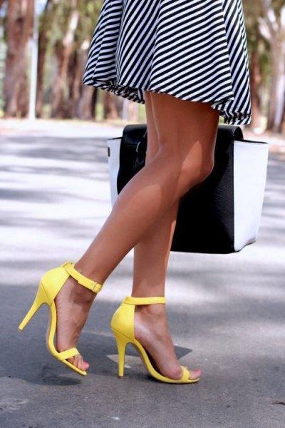 svart och vit diagonalt randig mini-passform och flare klänning med gula höga klackar med öppna tår