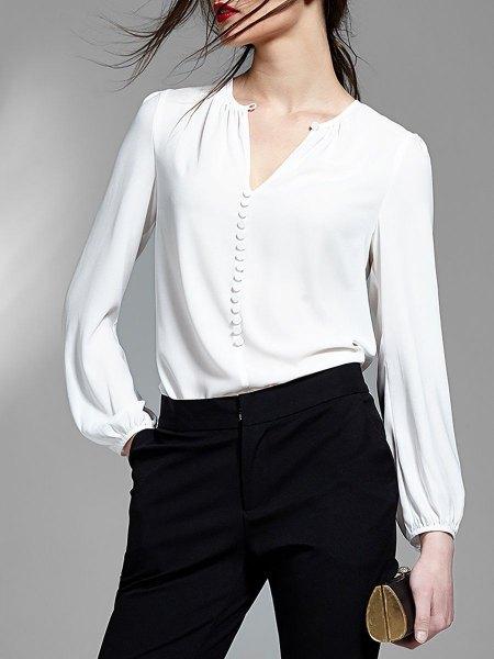 vit blus med V-ringning och svarta skinny jeans
