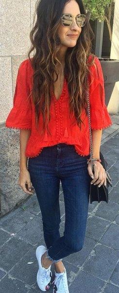 röd blus med V-ringning och mörkblå skinny jeans