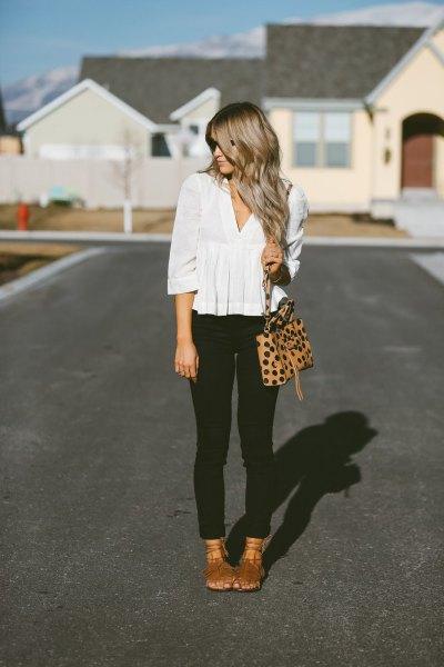 vit peplumblus med V-ringning och svarta ärmar och svarta skinny jeans