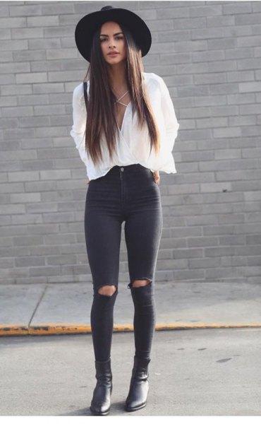 vit blus med svart filthatt och rippade skinny jeans