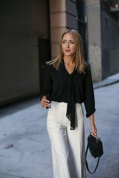 svart slipsblus med grå och vita randiga byxor med vida ben