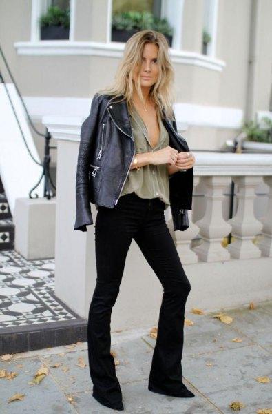 Läderjacka med grå blus med V-ringning och svarta utsvängda jeans