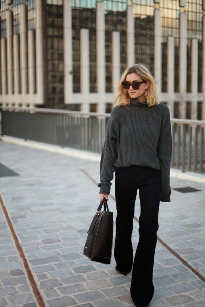 grå, tjock tröja med rund halsringning och svarta, utsvängda jeans