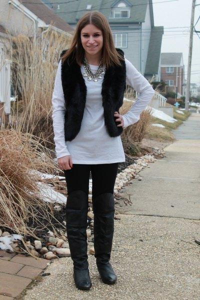 vit långärmad tunikatopp med svarta jeans och knähöga läderstövlar