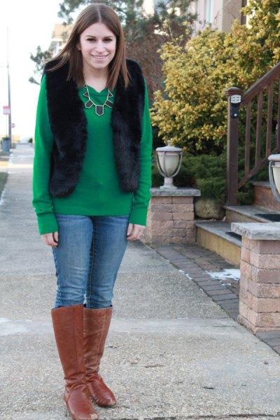 grön tröja med svart väst och knähöga stövlar av kamelmocka