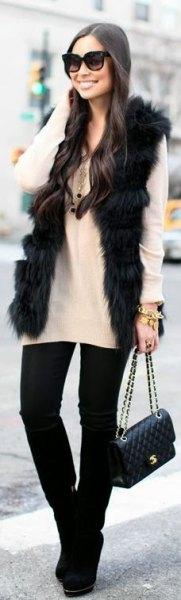 svart fuskpälsväst med vit tröja och svarta skinny jeans