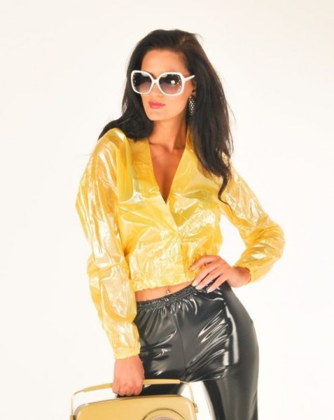 gul bomberjacka av plast med matchande svarta byxor