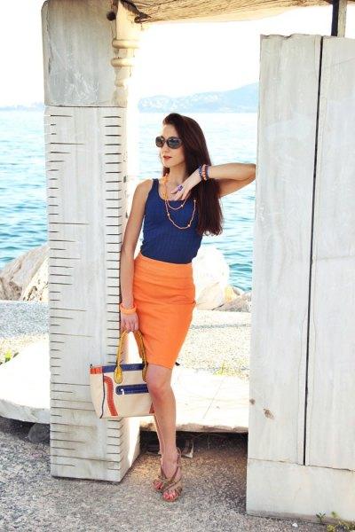 Mörkblå västtopp med en knälång kjol i orange