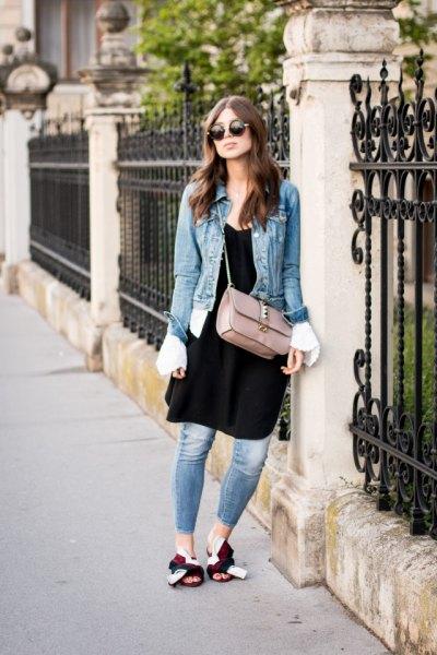 blå denimjacka med svart tunikaklänning och tofflor i guld