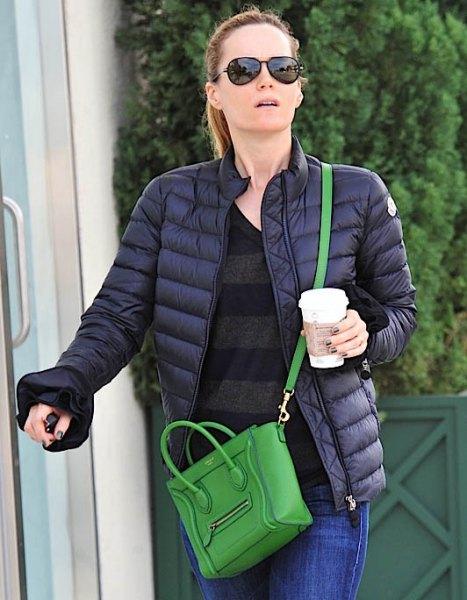 svart dunjacka med blå jeans och handväska i brunt läder