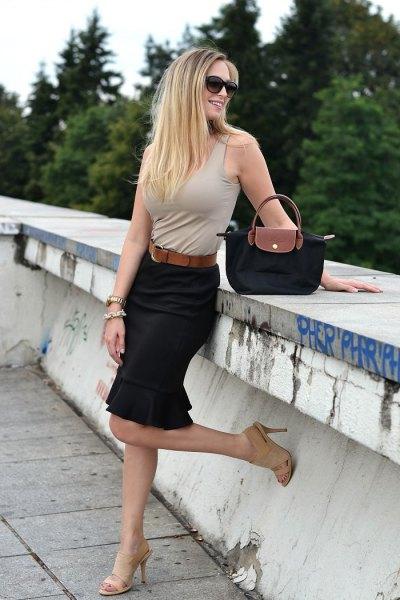 Ljusrosa ärmlös topp med svart penna kjol och liten handväska