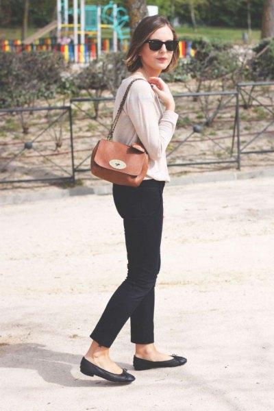 Elfenbenskofta med svarta, beskurna jeans och en liten brun axelväska
