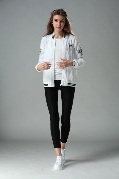 Bomberjacka med svarta, korta leggings och vita sneakers