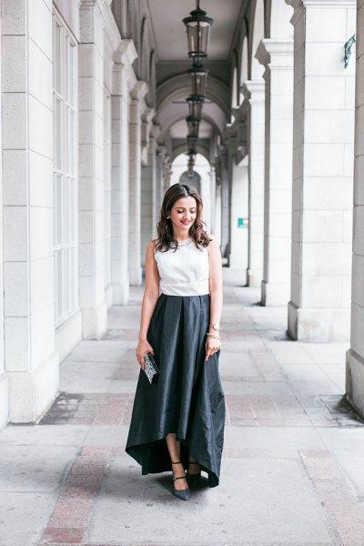 vit ärmlös blus med svart maxi hög-låg flare klänning och kopplingsväska