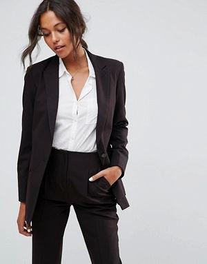 överdimensionerad kostymjacka med vit skjorta med knappar och byxor med hög midja