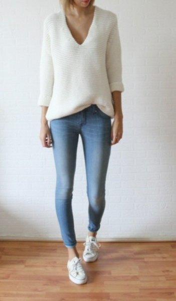 vit stickad tröja med avslappnad passform och V-ringning och ljusblå skinny jeans