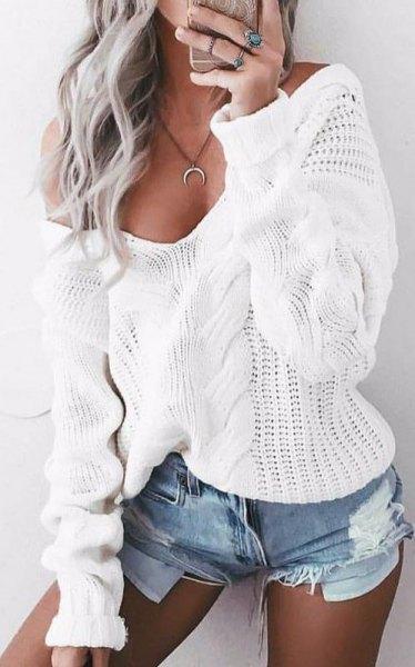 vit kabelstickad tröja med vid V-ringning och blå mini-jeansshorts