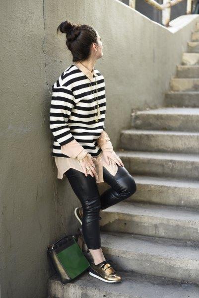 svartvitt randig långärmad tröja med läderbyxor och bronsfärgade metalliska sneakers