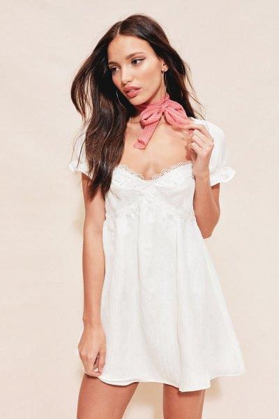 djupvit babydockklänning med v-ringning, rosa halsduk