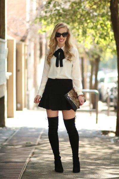vit och svart fluga blus med skridsko kjol och overknee stövlar