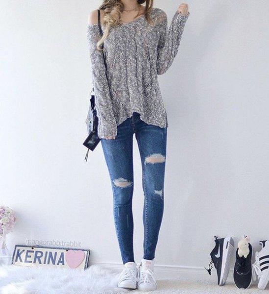 ljunggrå stickad tröja med en axel och blå skinny jeans