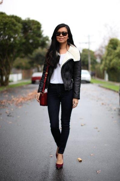 svart flygjacka med vit pälskrage och smala jeans