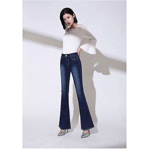 vit topp med klockärmar och mörkblå jeans med hög klockbotten