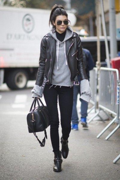 svart bikerjacka i läder med grå huvtröja och moto stövlar