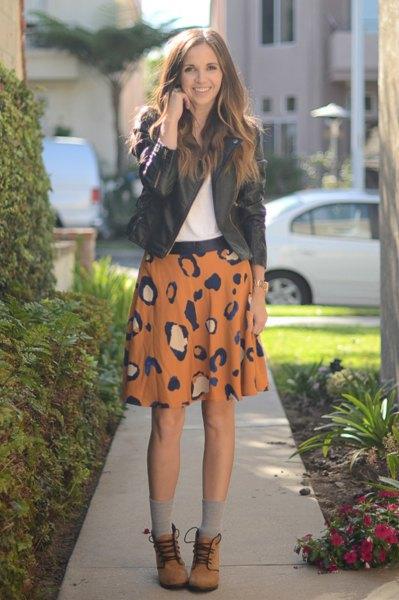 svart läderjacka med orange tryckt minikjol och snörade ankelstövlar