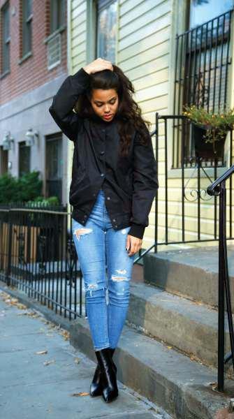 svart jacka med blå skinny jeans och läderstövlar